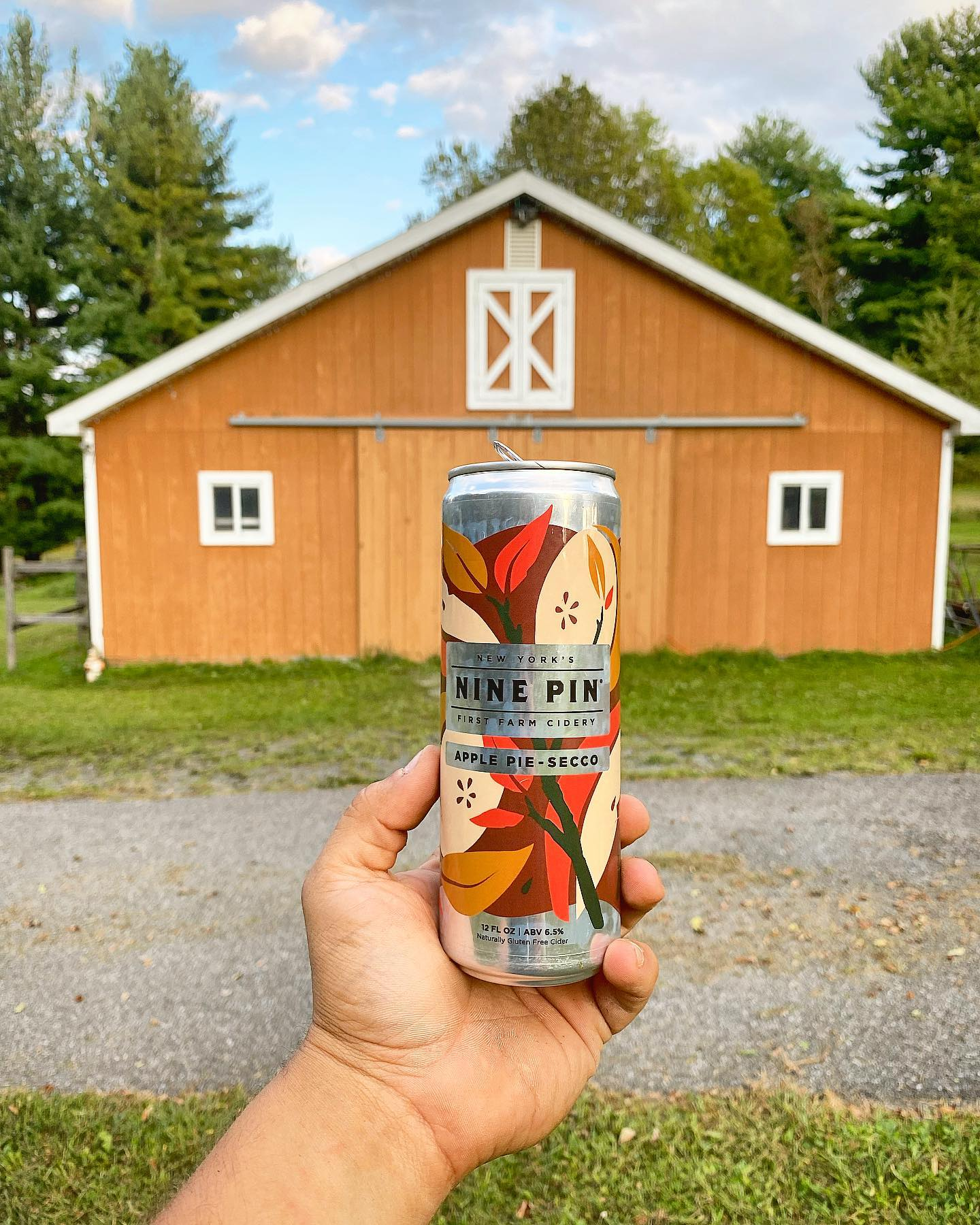 Can of Nine Pin Apple Pie-Secco can in front of red barn.