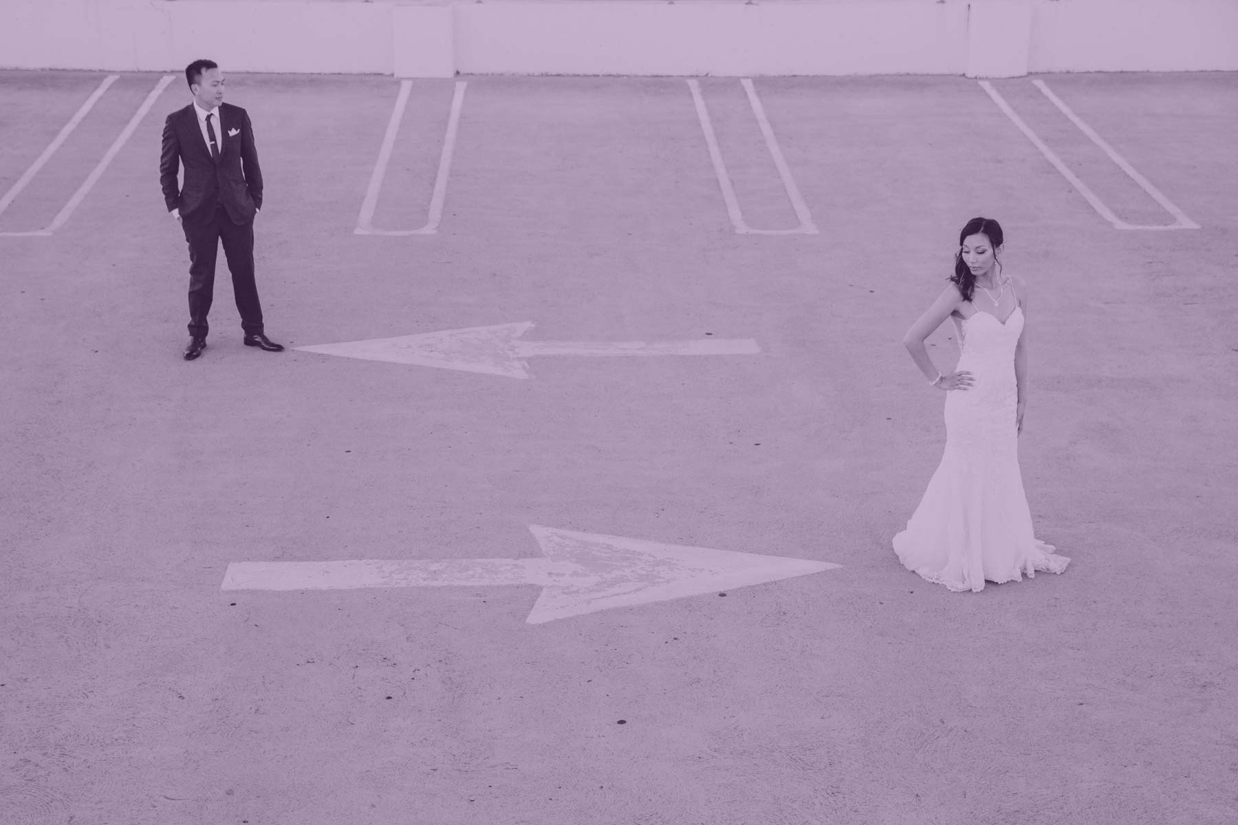 Groom and bride posing at an empty parking garage