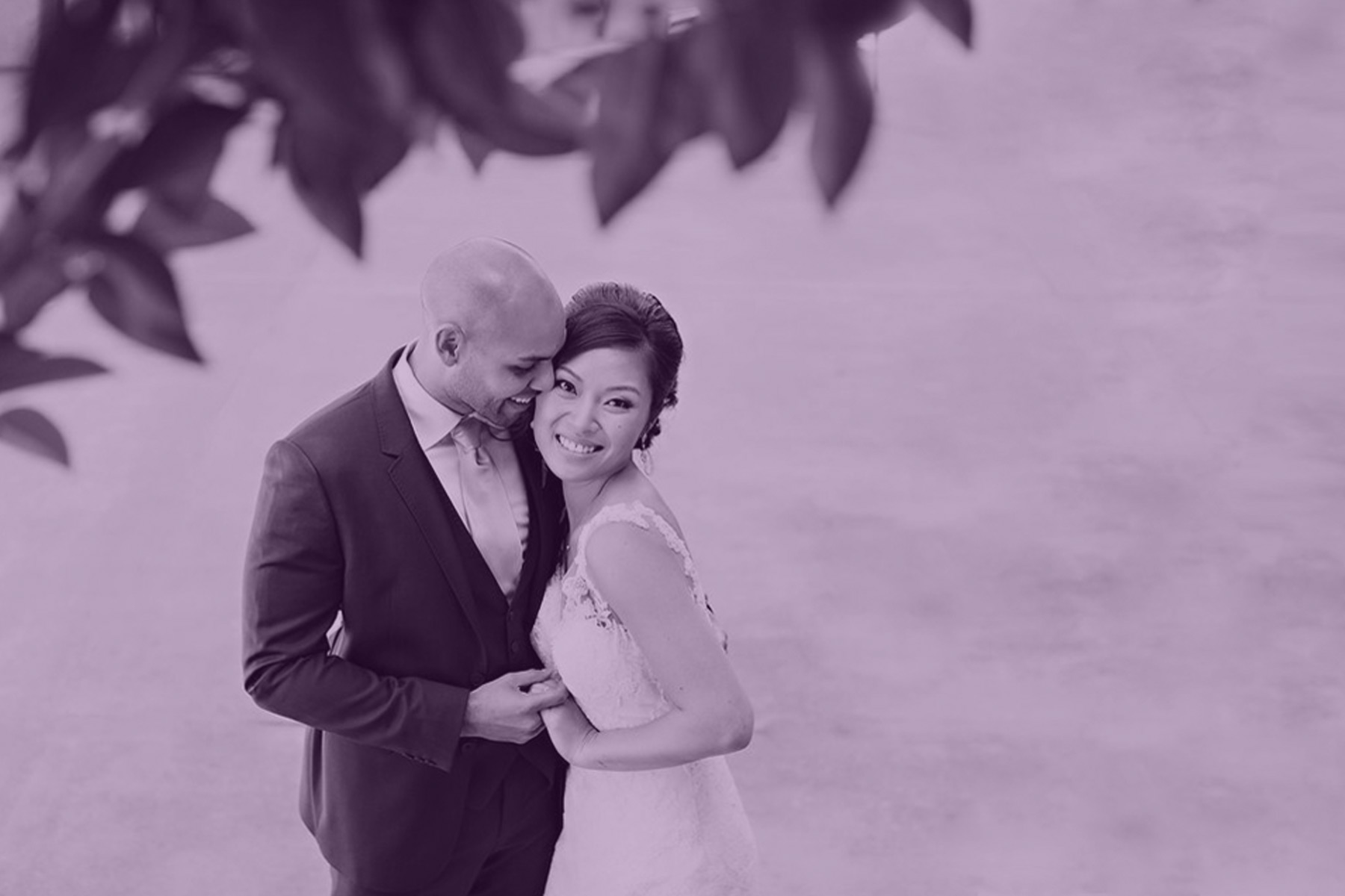 Groom and bride in an embrace under a tree