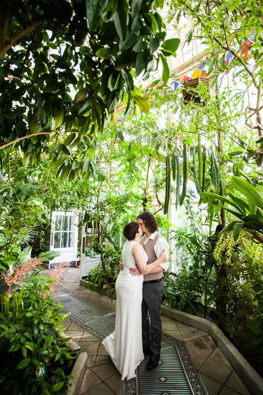 Bride and groom kissing inside a greenhouse