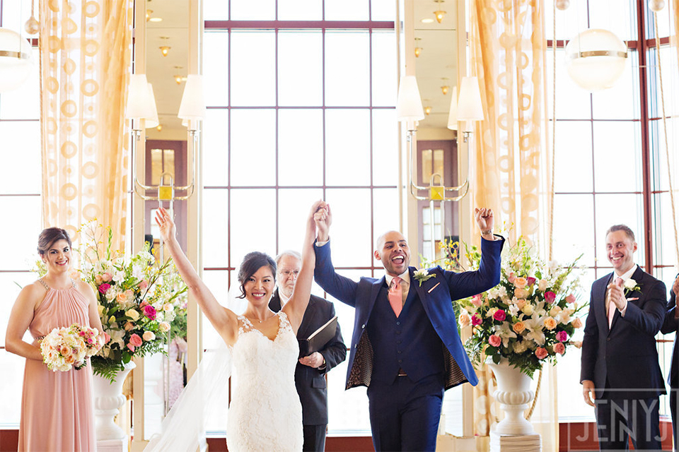 Bride and groom with their hands in the air at the altar