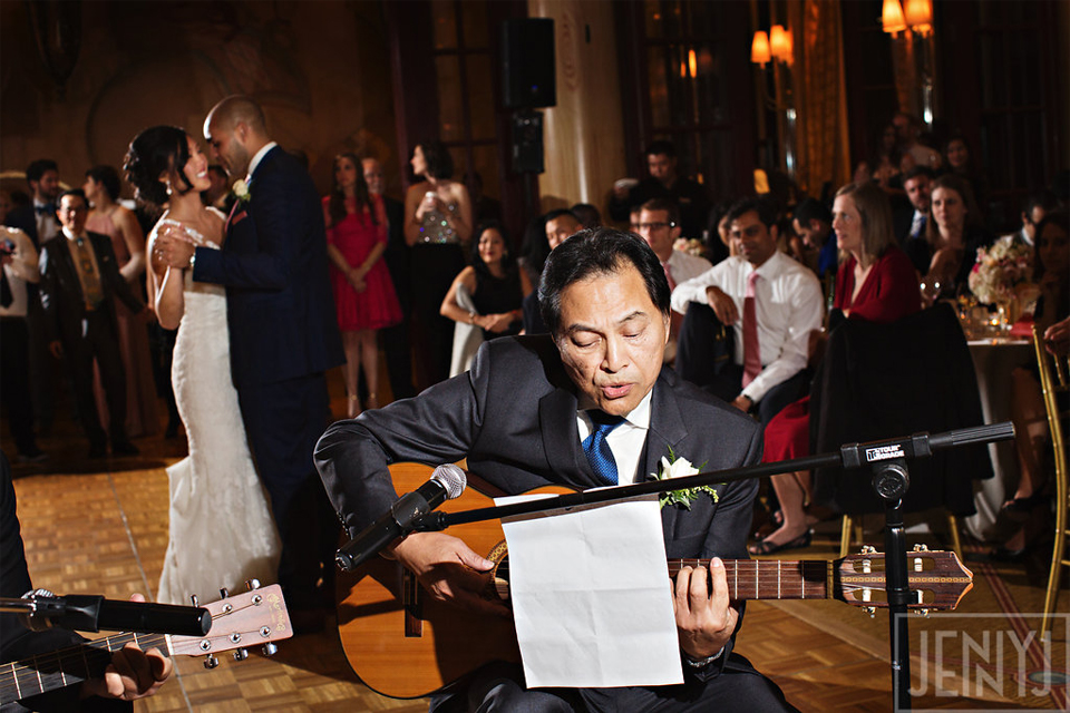 Father of the bride playing guitar while bride and groom dance