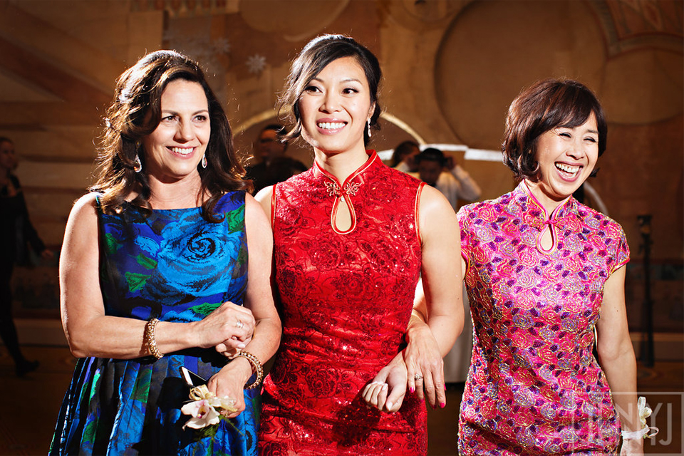 Bride wearing qipao locking arms with mother and mother-in-law