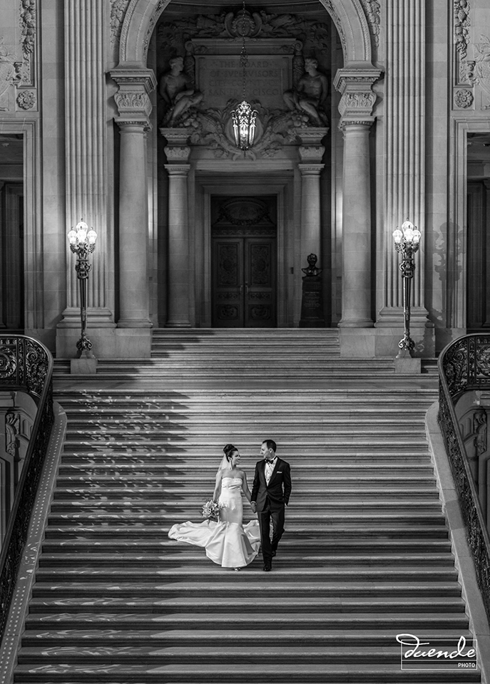 Bride and groom walking down the stairs in San Francisco City Hall