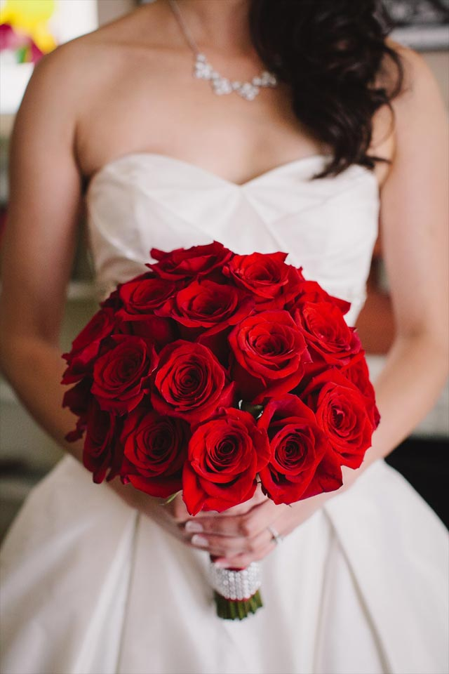 Bride holding wedding bouquet of red roses