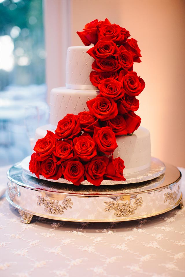 Red roses cascading down a white wedding cake