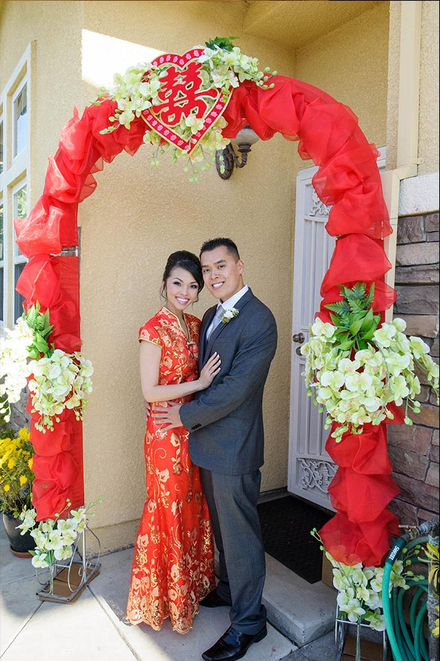 Bride in red cheongsam and groom in suit under floral arch
