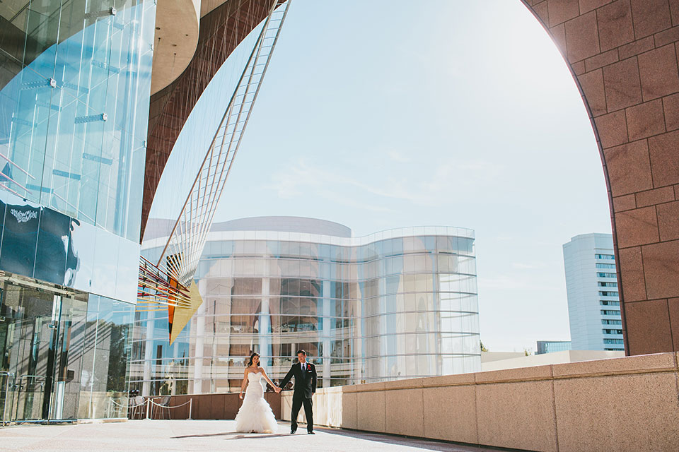 Bride and groom holding hands at Segerstrom Center for the Arts in Costa Mesa, California
