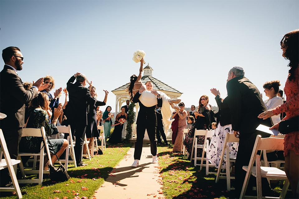 Groom carrying bride down the aisle