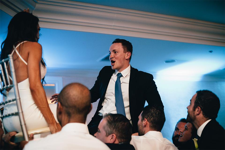 Bride and groom lifted on chairs on the dance floor