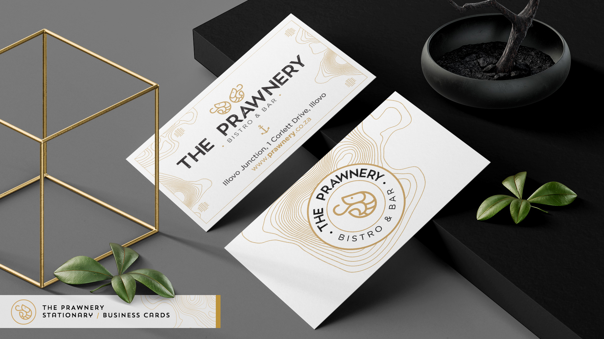 Business cards lying on a black desk with leaves and ornaments