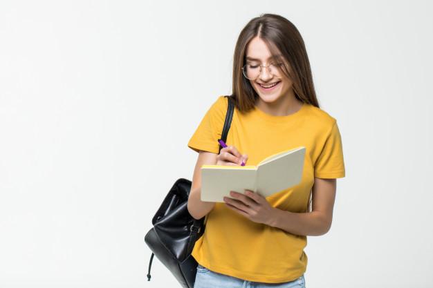 Jovem de, aproximadamente, 17 anos, usando uma blusa amarela, uma calça jeans, um óculos com armação transparente e uma mochila preta. Ela está escrevendo em seu caderno com uma caneta roxa.