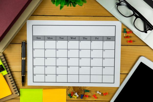 Mesa de madeira com diversos objetos em sua superfície. Calendário para ser organizado e preenchido, blocos adesivos, tablet, cadernos, , alfinetes, óculos, cadernos e caneta.