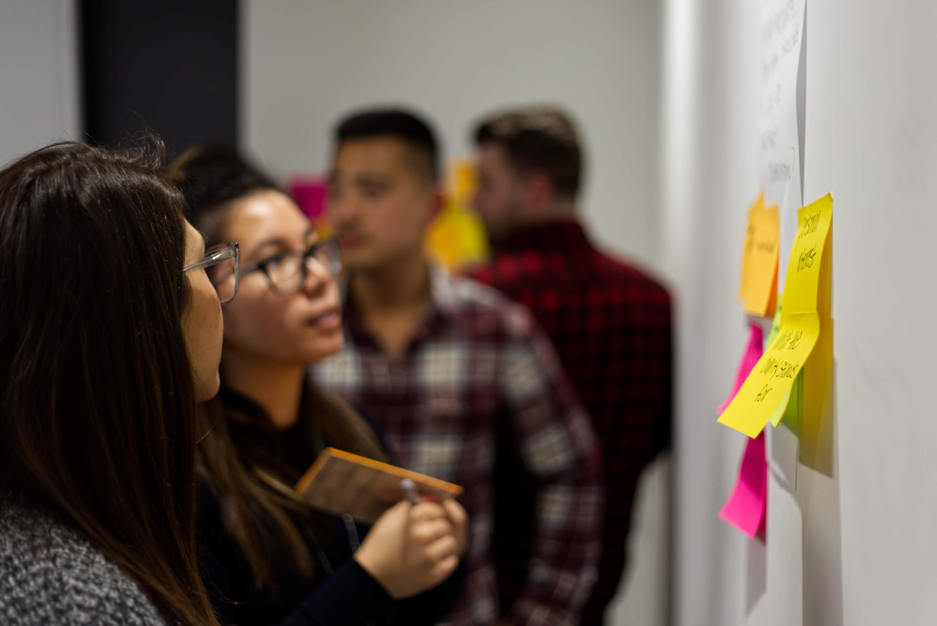 Two women with post it notes, discussing a problem near a whiteboard