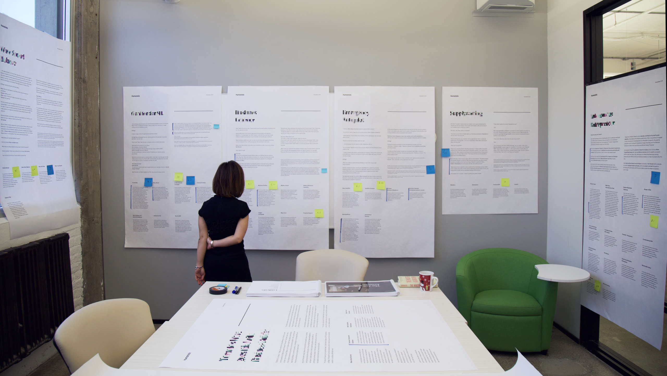 A woman stands in a board room, looking at large posters of a project deliverables