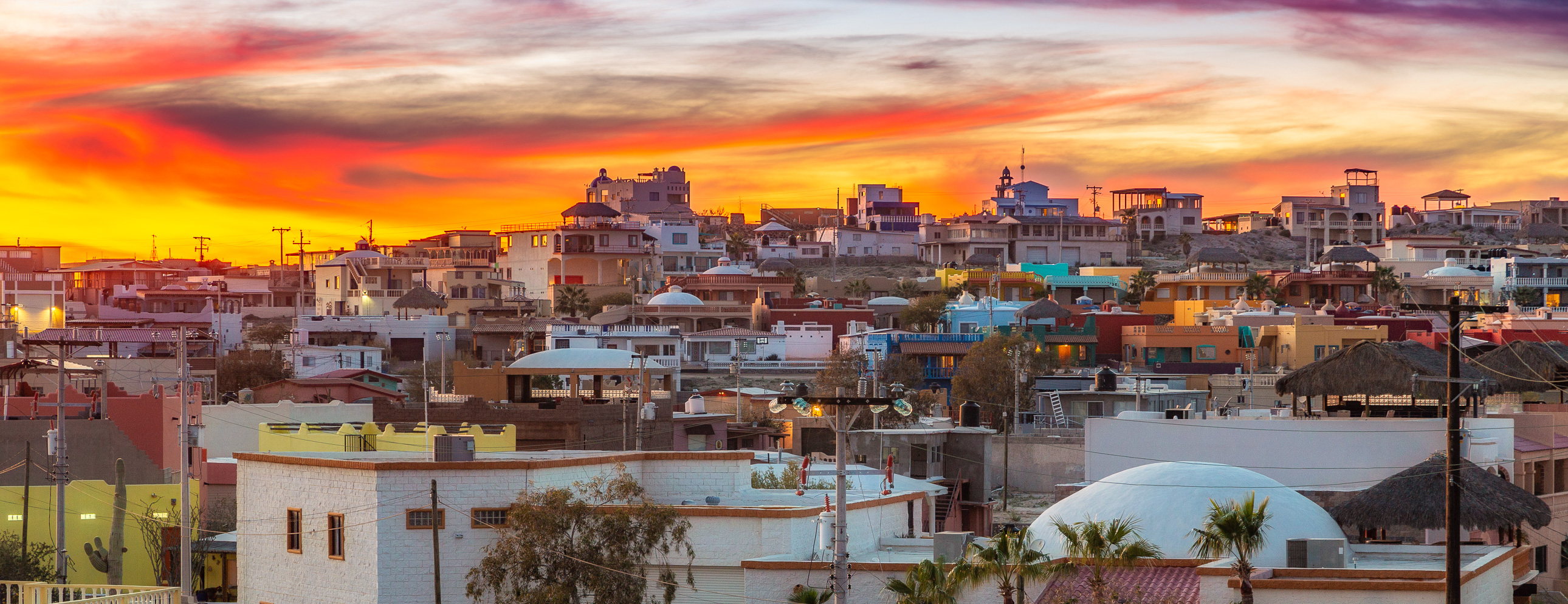 Panoramic photo of a glowing sunset and small houses of Cholla Bay community in Mexico