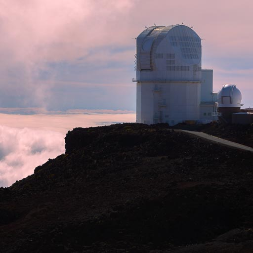 Photo of the Haleakala Observatory with pink clouds in the distance
