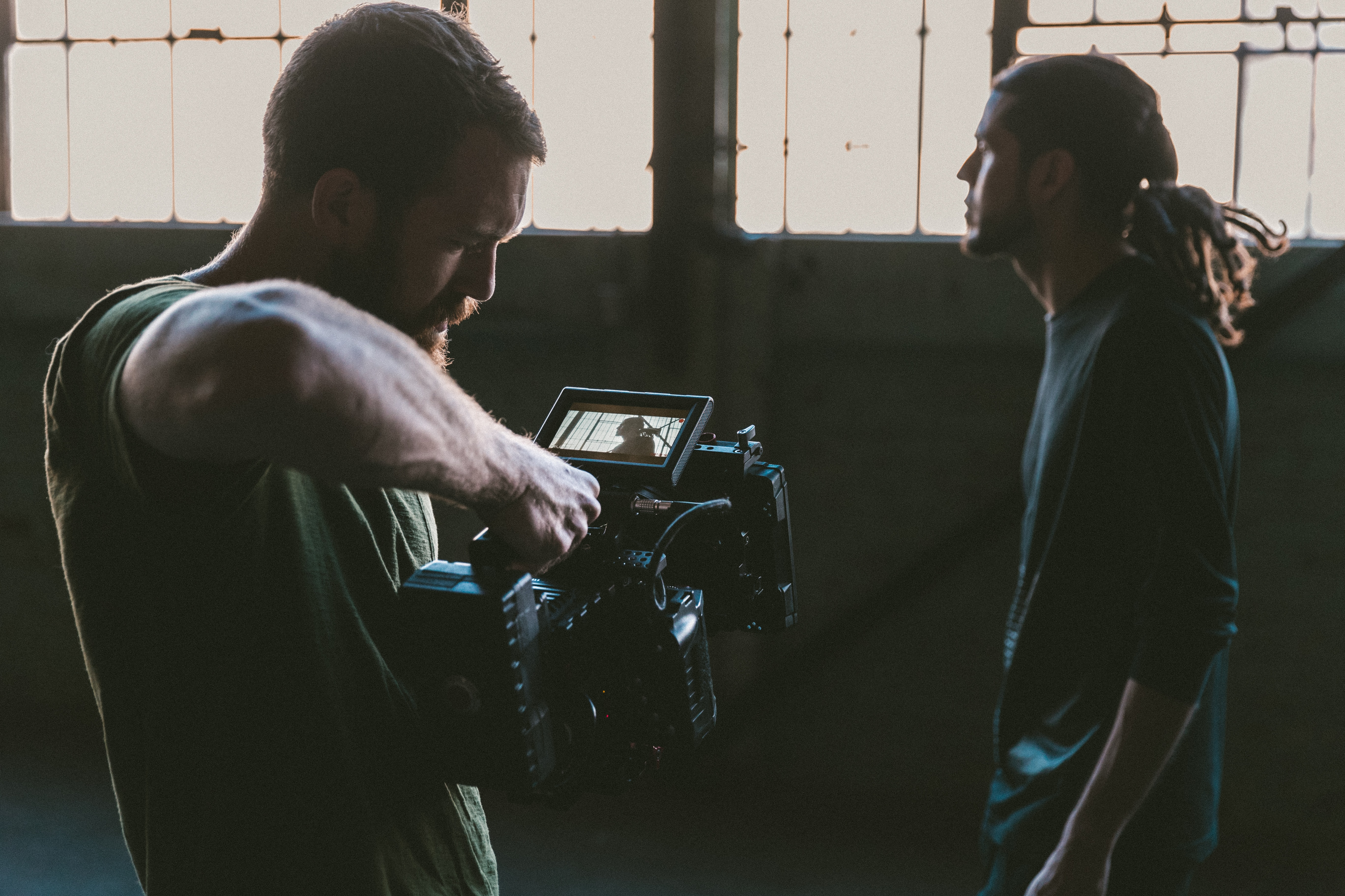 A man holding a professional video camera in an indoor environment