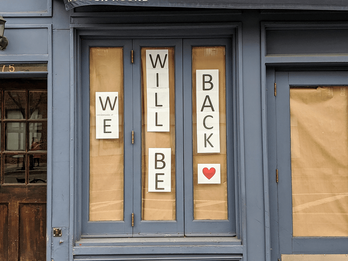 "Papered over windows of a small business with the words ""We Will Be Back"" pasted on the windows"
