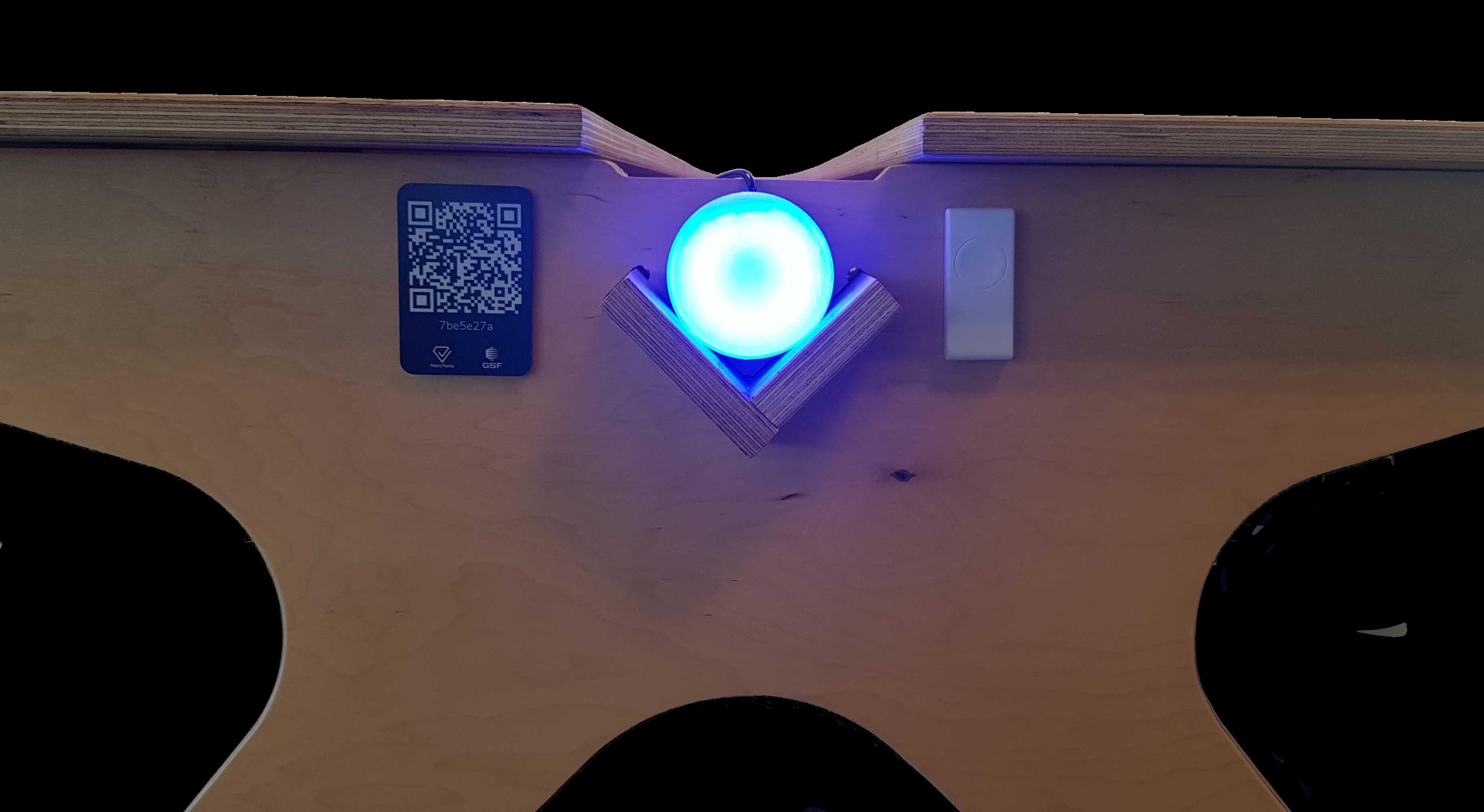 Photo d'un espace de travail avec QR code, bouton connecté et led allumée
