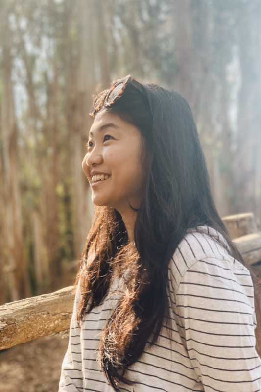 A girl smiling, with sun shining