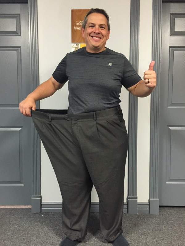 Skinny man standing in larger pants showing significant weight loss