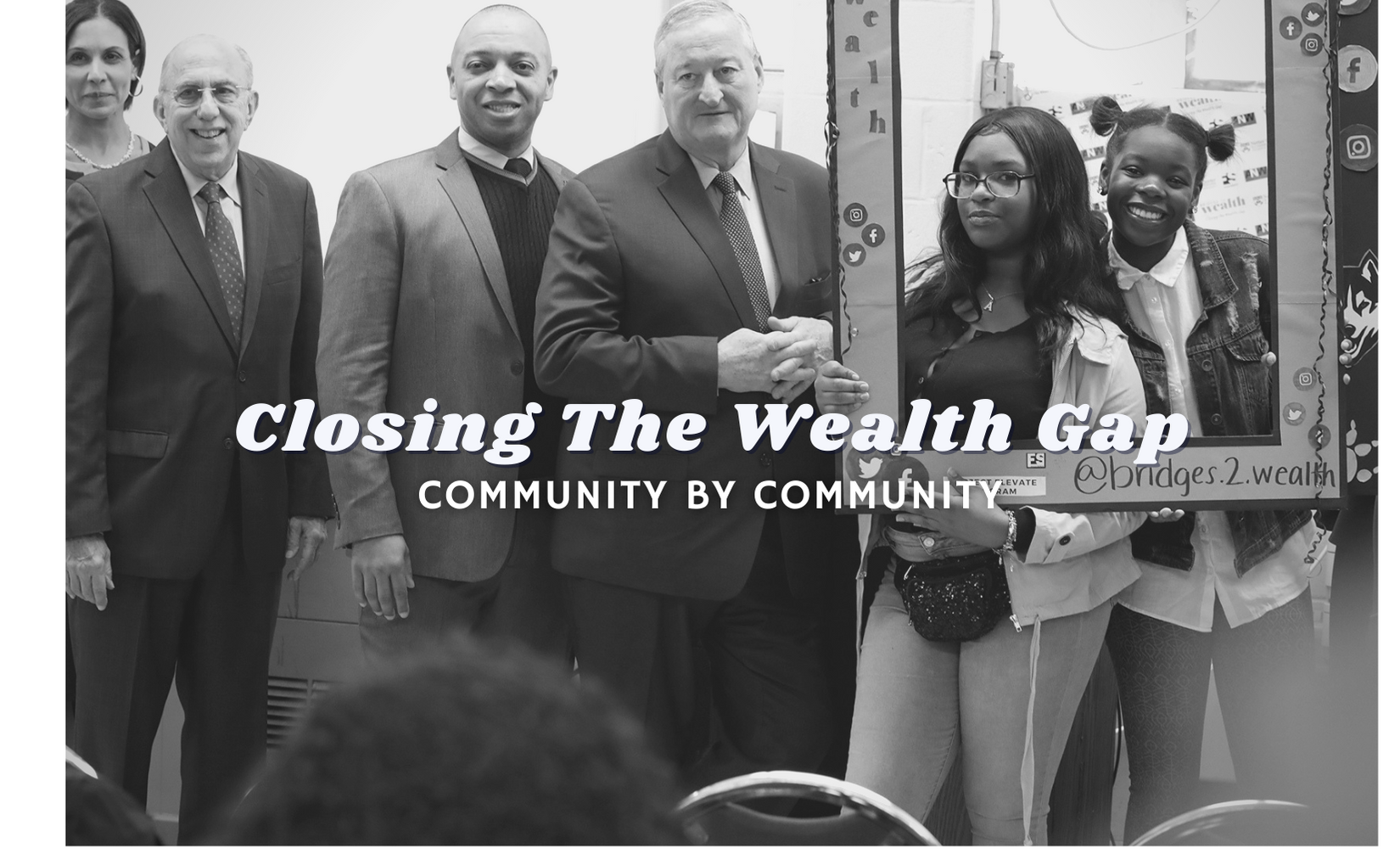 A black and white image of high school students receiving a grant award through the Bridges to Wealth program.