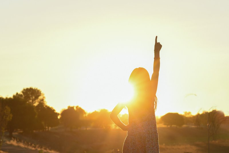 silhouette of a girl pointing up
