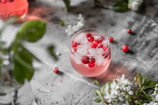 top view spring cranberry lemonade in a glass on a gray shabby table with cherry flowers and leaves - cranberry fizz stock pictures, royalty-free photos & images