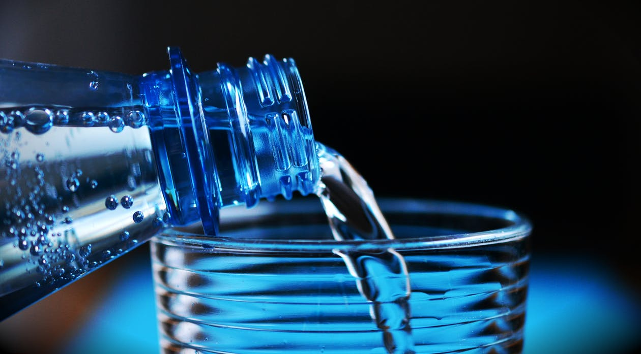 Close-up of Bottle Pouring Water on Glass