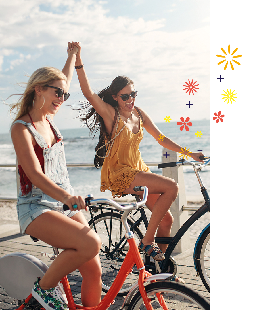 Two women riding bikes while holding hands