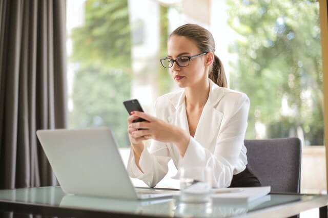 serious-businesswoman-using-smartphone-in-workplace