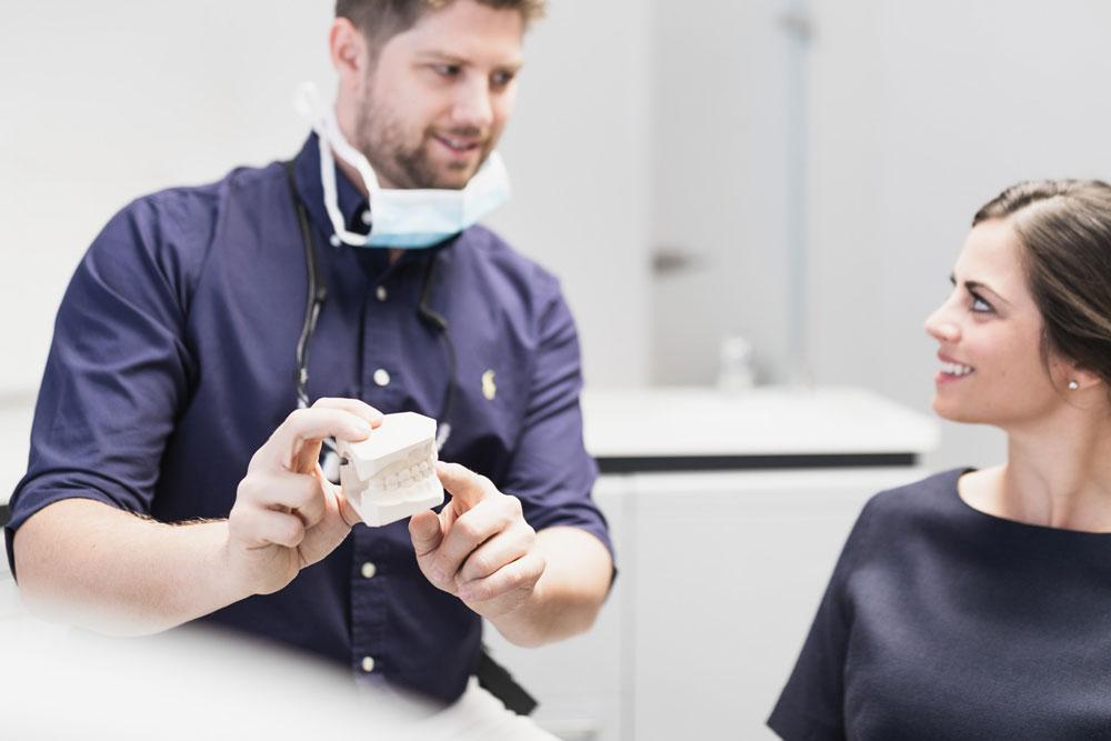 Zahnarzt Marvin Reuter in Beratung mit Patientin
