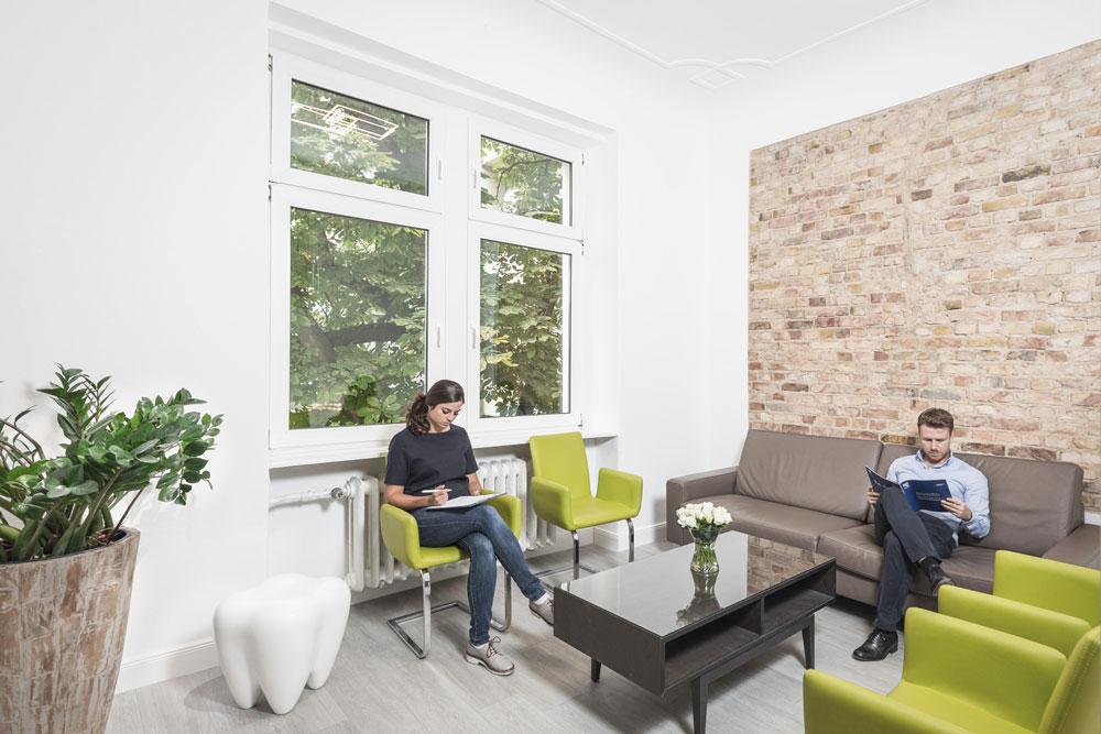 Patienten der Zahnarztpraxis Reuter im modernen Wartezimmer
