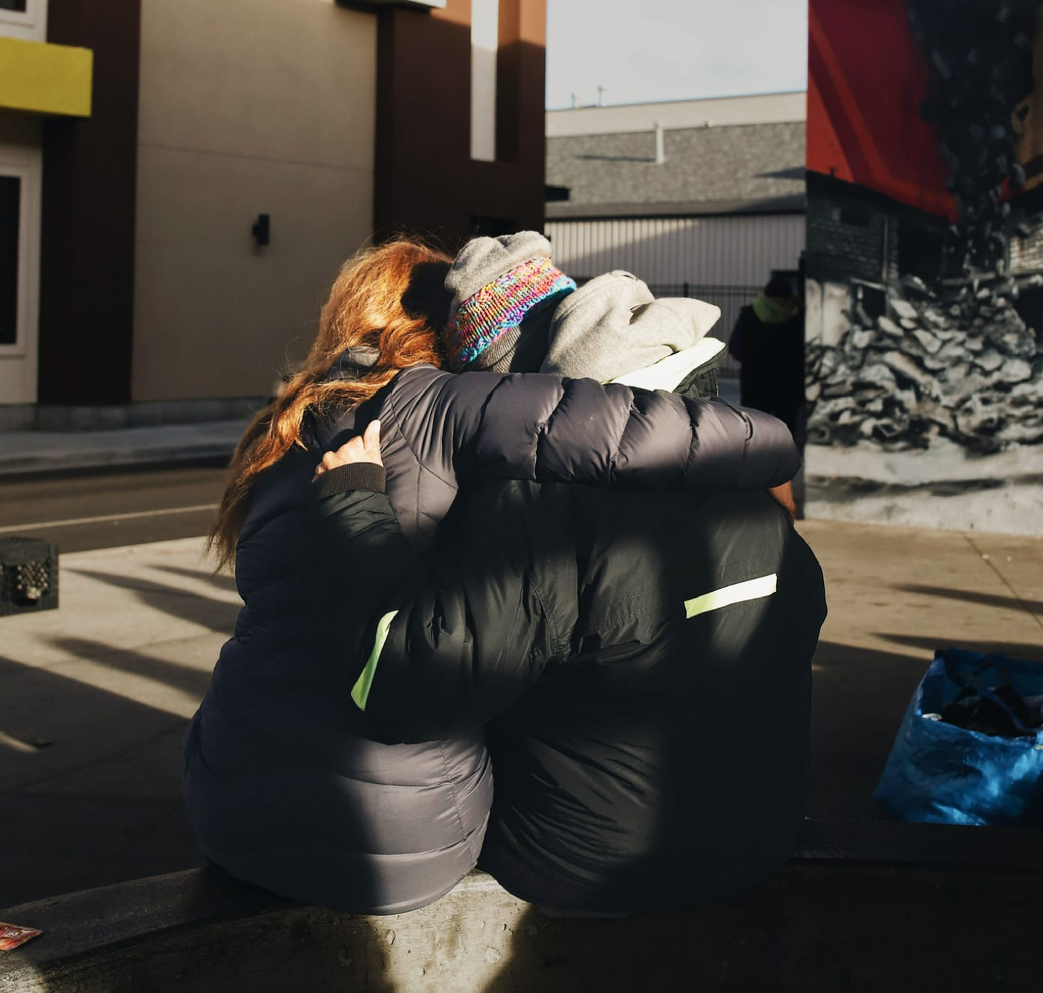 A Neighbor Idaho volunteer hugging a homeless person