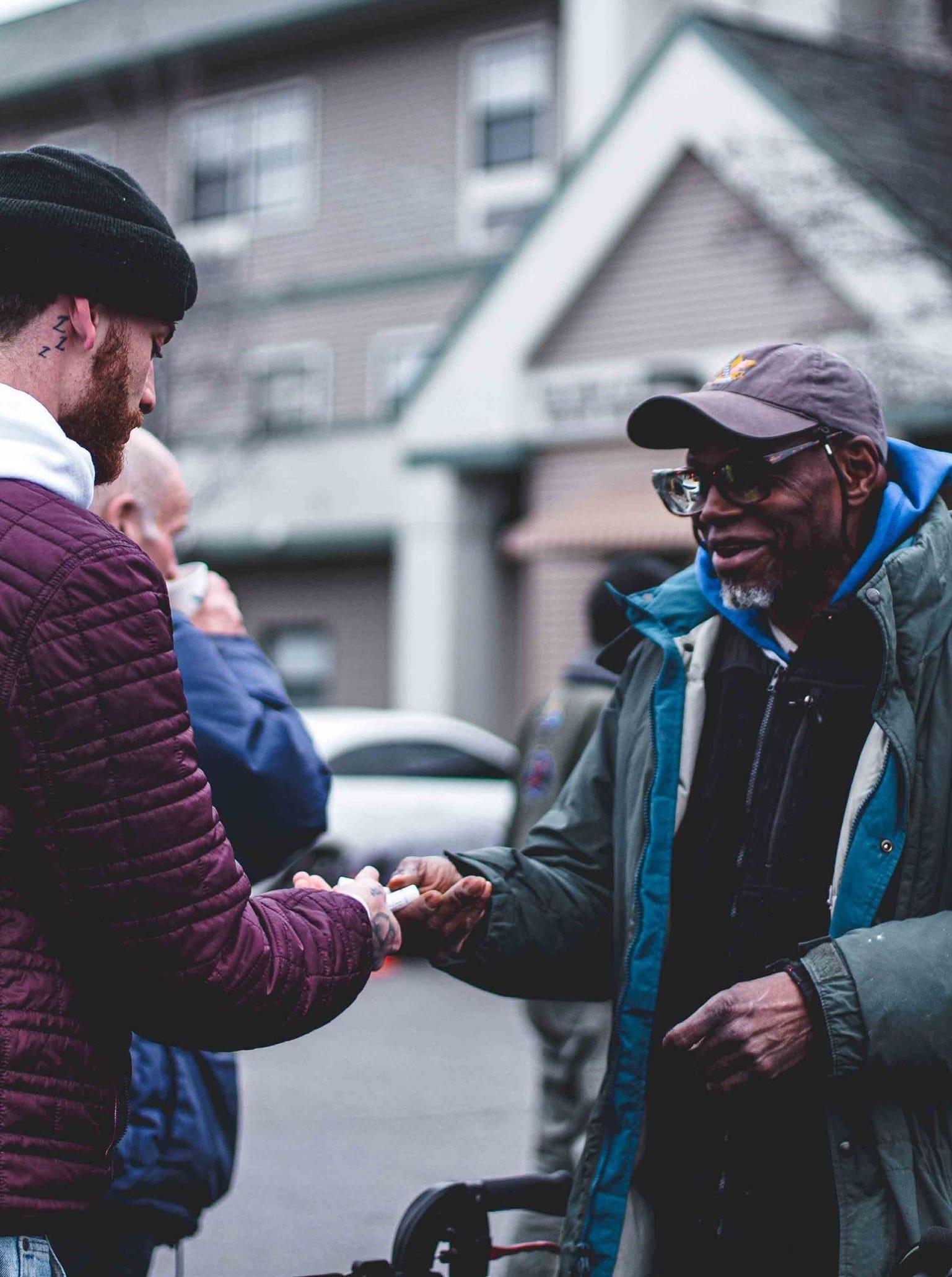 A volunteer giving a man chapstick