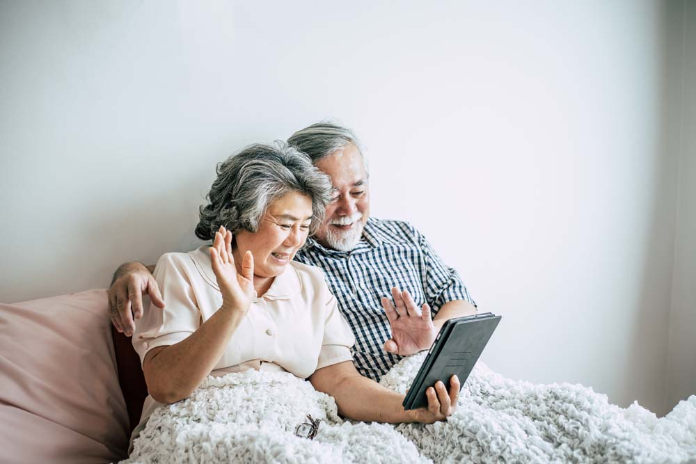 Older couple on sofa using video calling on tablet device