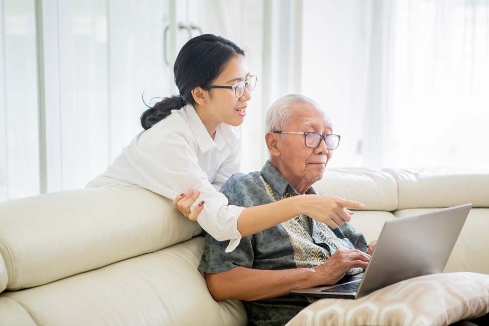 Older person using laptop on sofa being assisted by carer