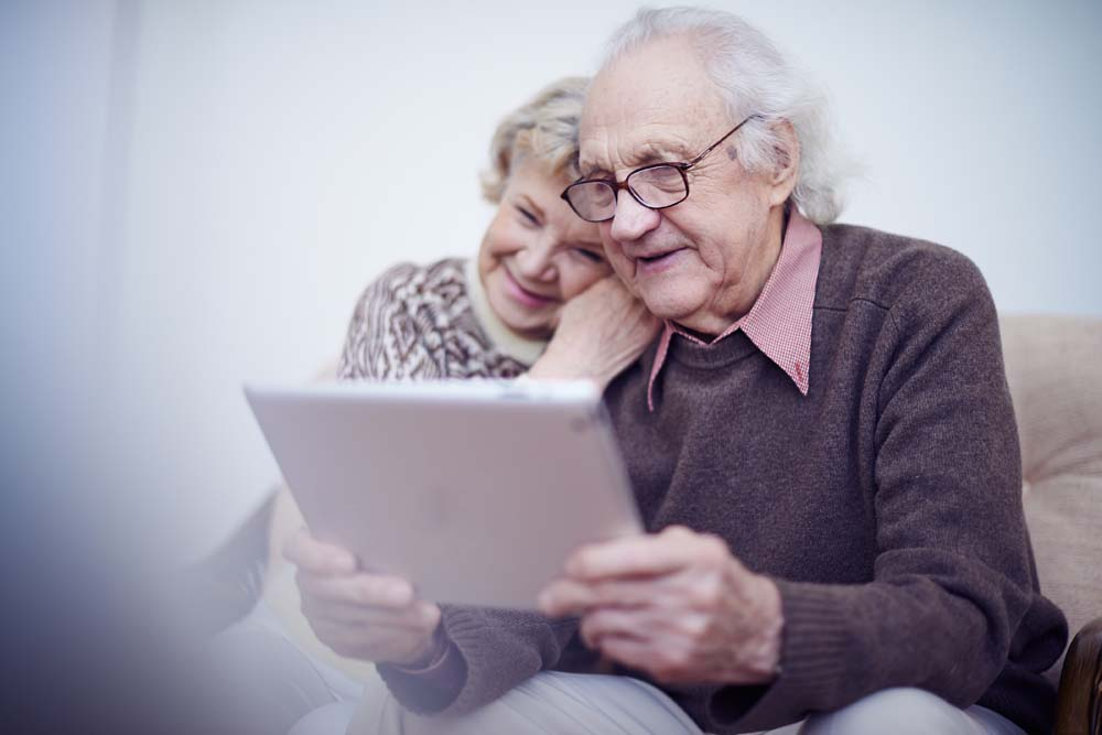 Happy older couple using tablet device on sofa together