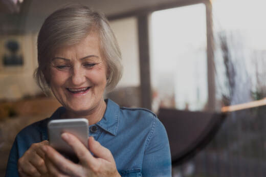 Older woman using smartphone at home