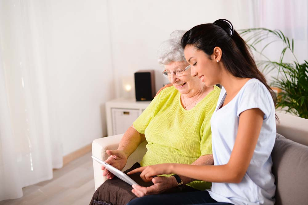 Older person using tablet device being assisted by daughter
