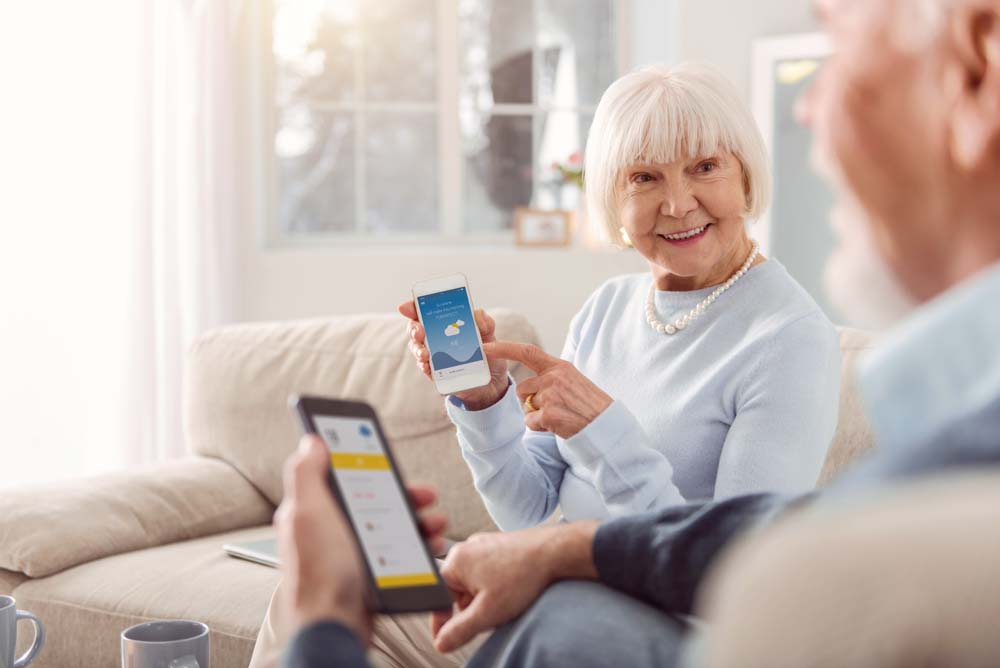 Older couple using smartphones on sofa