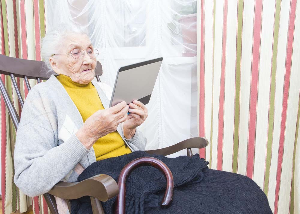 Older person using tablet device in rocking chair