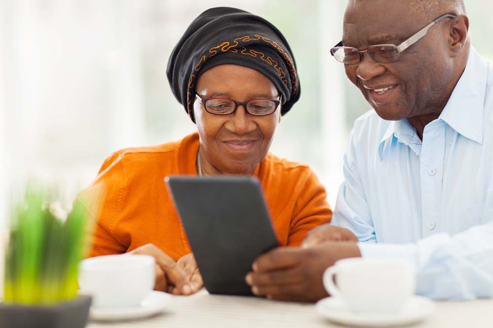 Older couple using tablet device at table