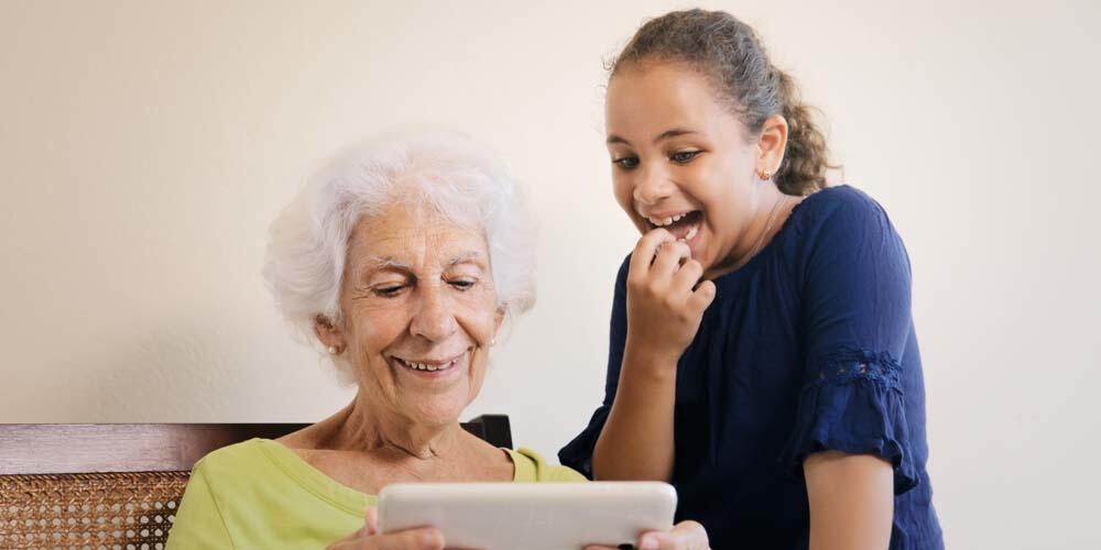 Older woman using tablet device with granddaughter