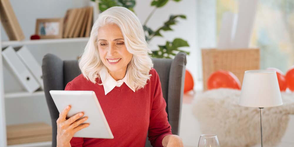 Older woman holding tablet device