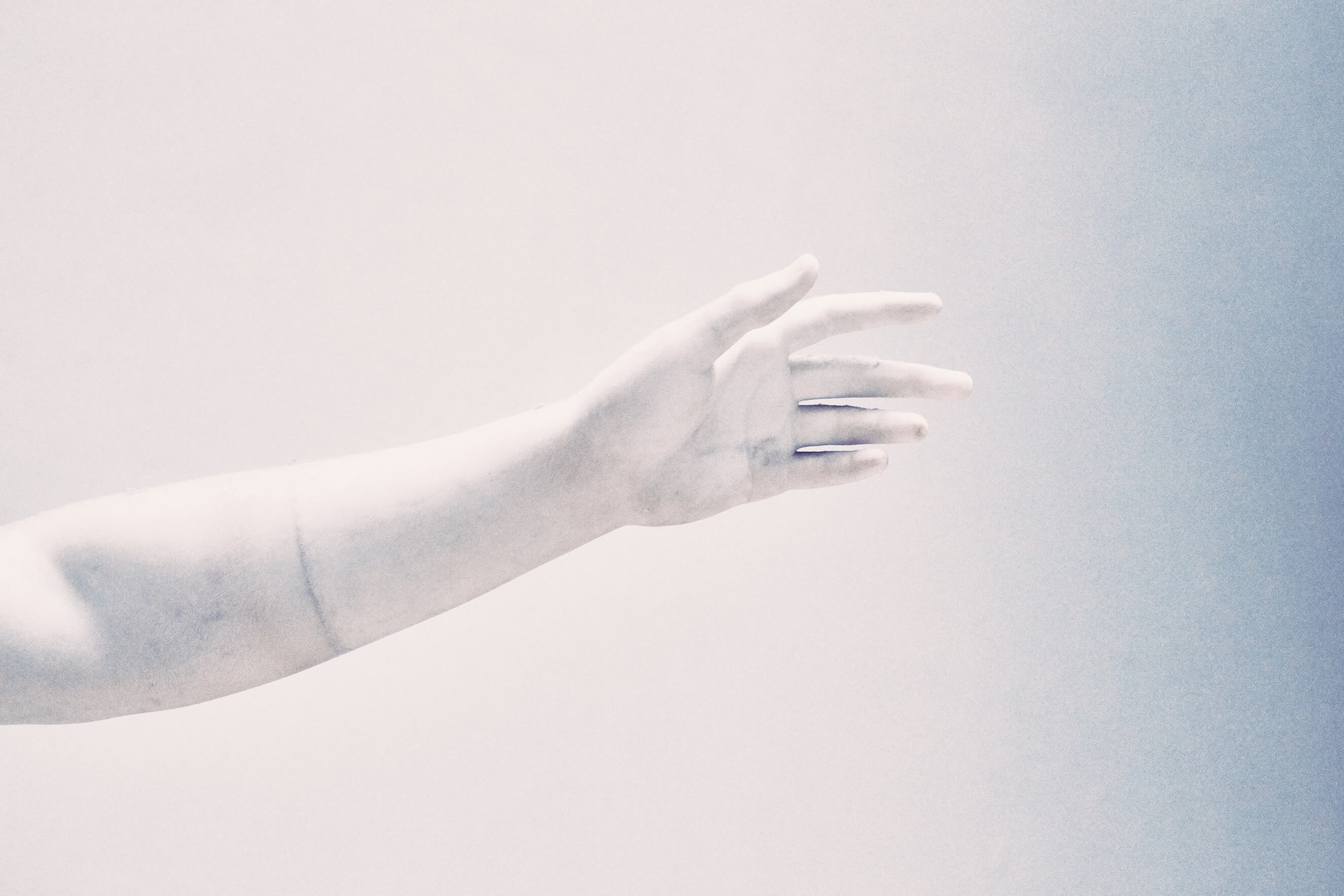 A marble statue's arm outreached on a blank background
