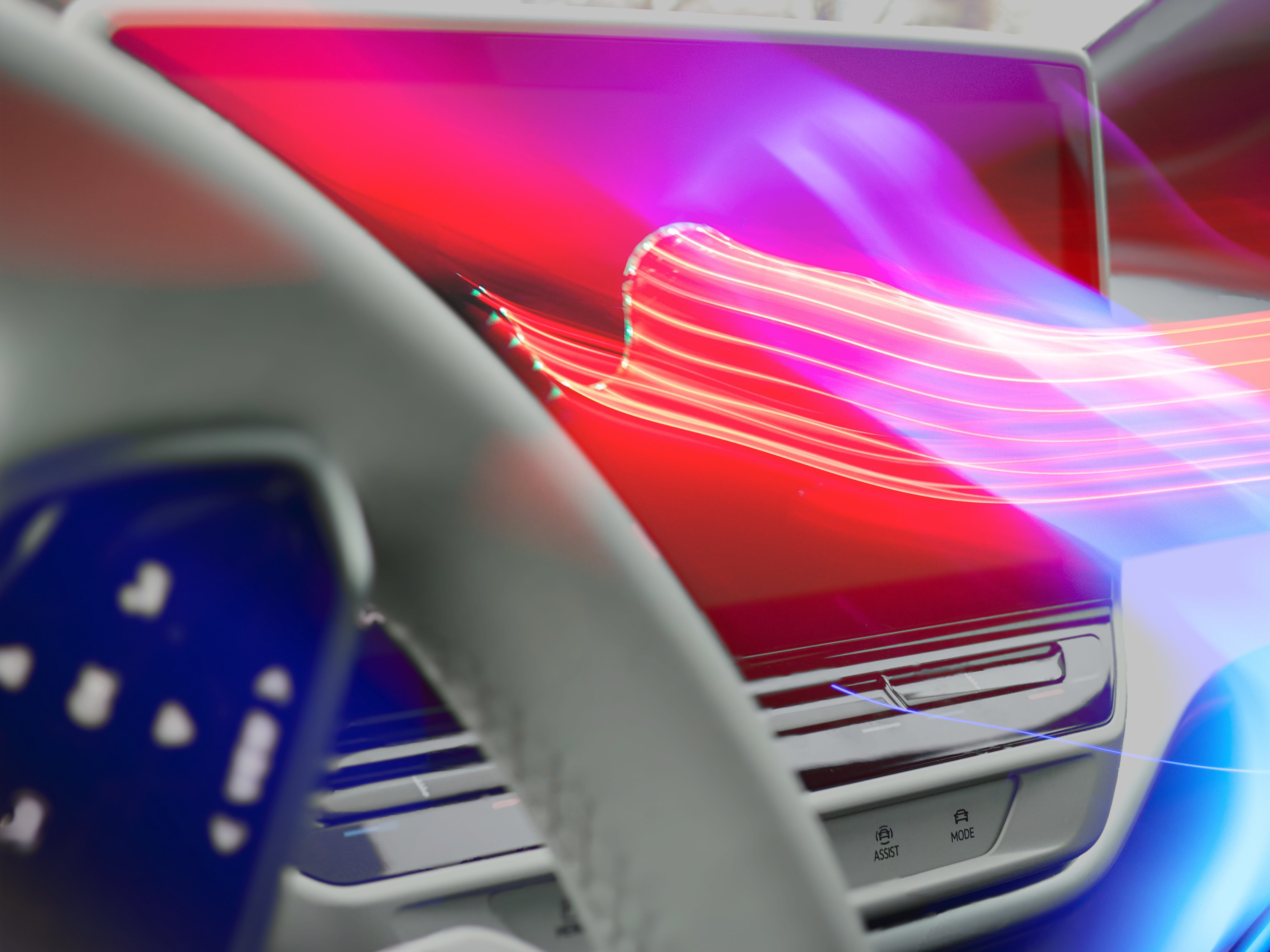 A close-up image of a white steering wheel with a blank infotainment system behind glowing with streaks of pink, red, and blue light.