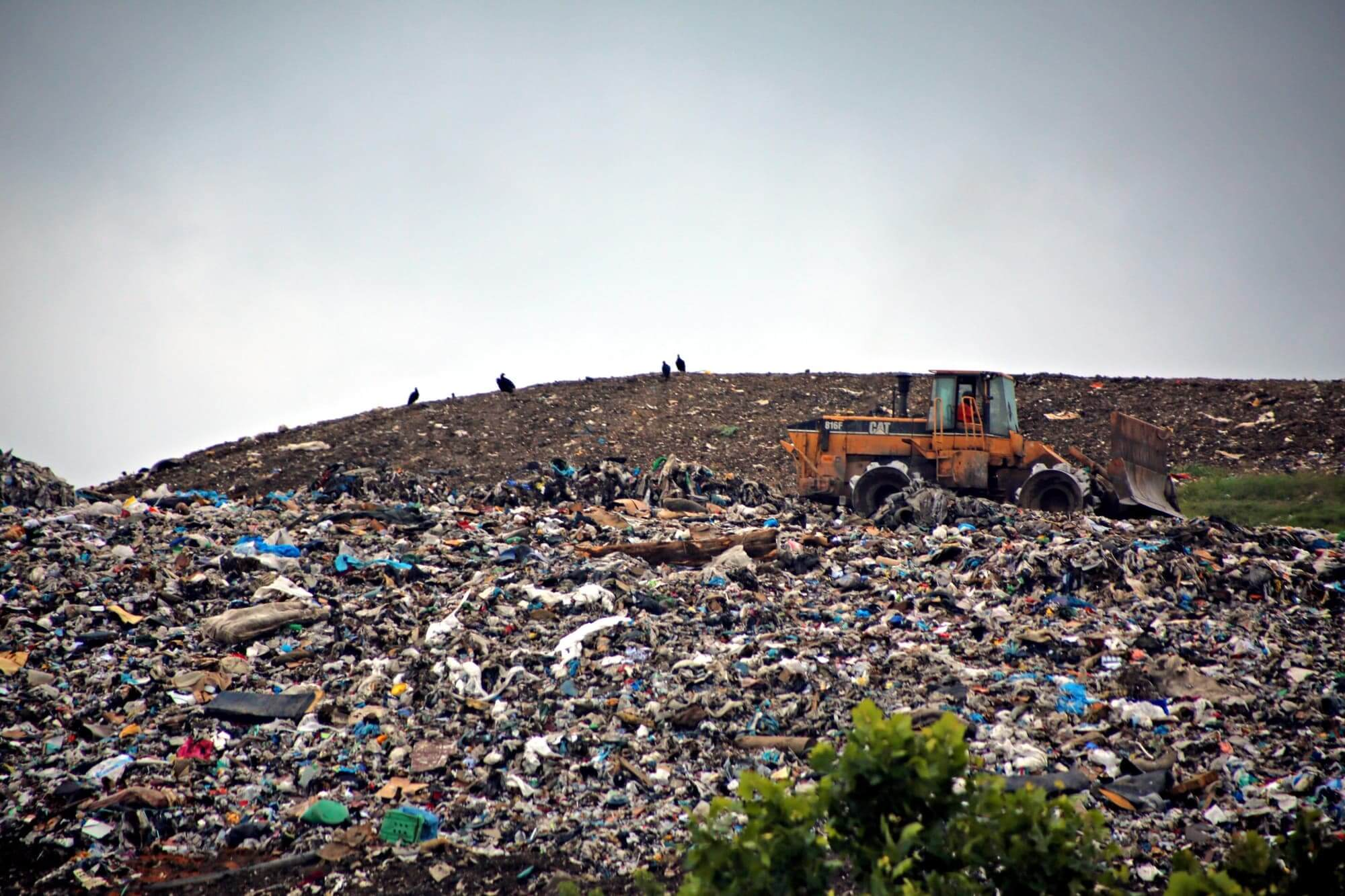 Picture of landfill with trash, people, and yellow bulldozer.