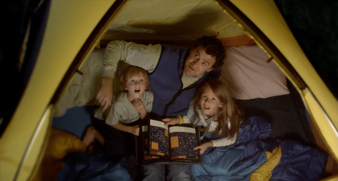 This bank of America commercial features a father and his two kids in a tent having pillow fights, reading stories, and star gazing.